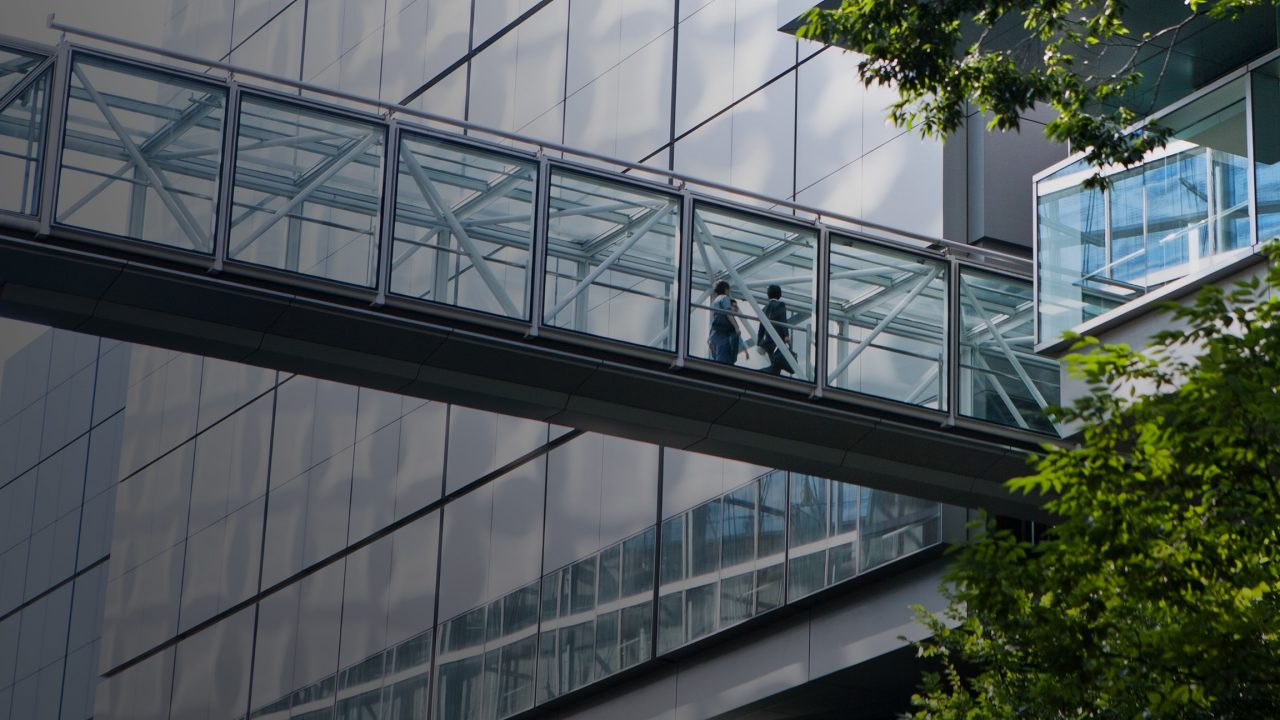 Employees walking across a glass bridge into a building
