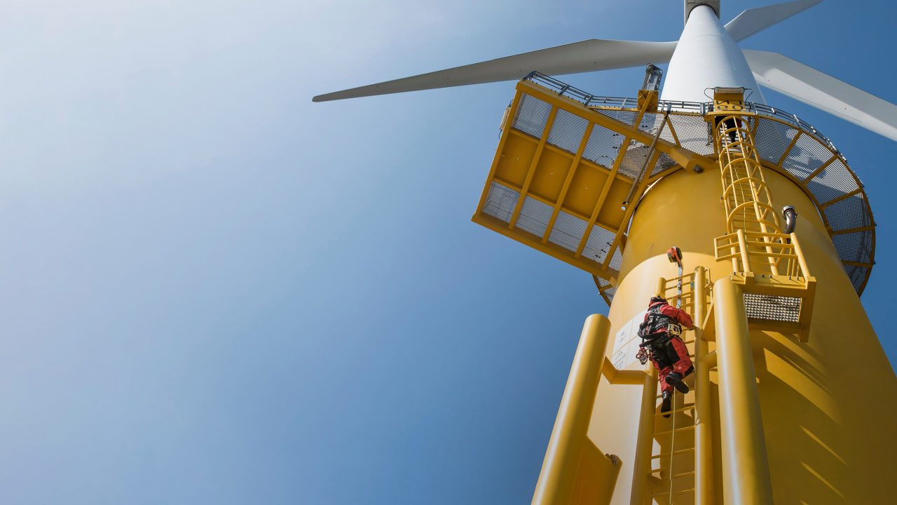 Worker climbing the outside of a wind turbine on the outside