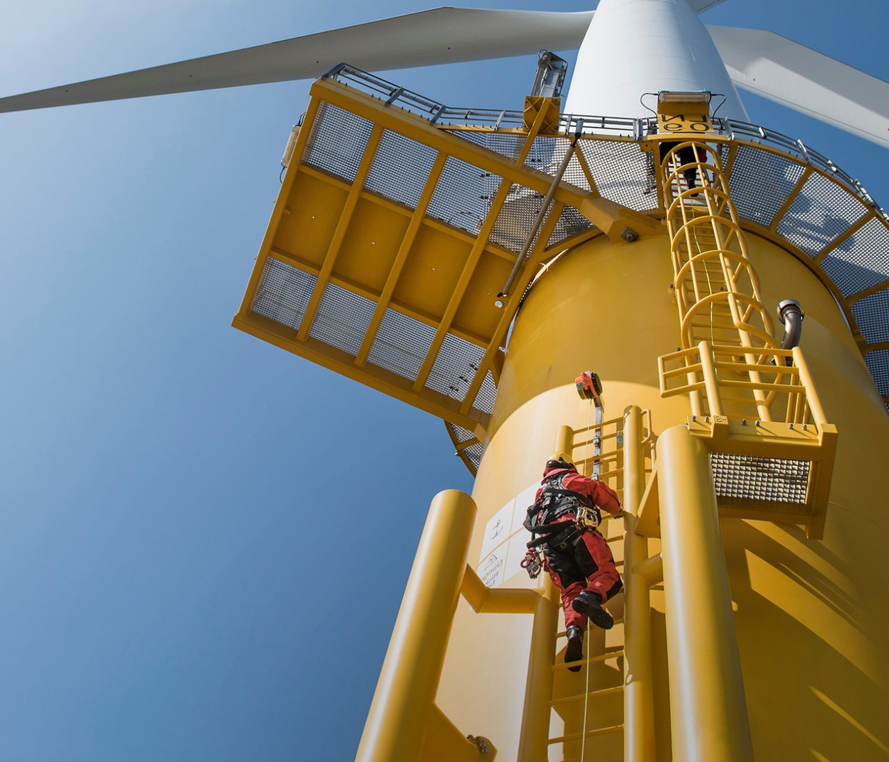Worker climbing a wind turbine on the outside